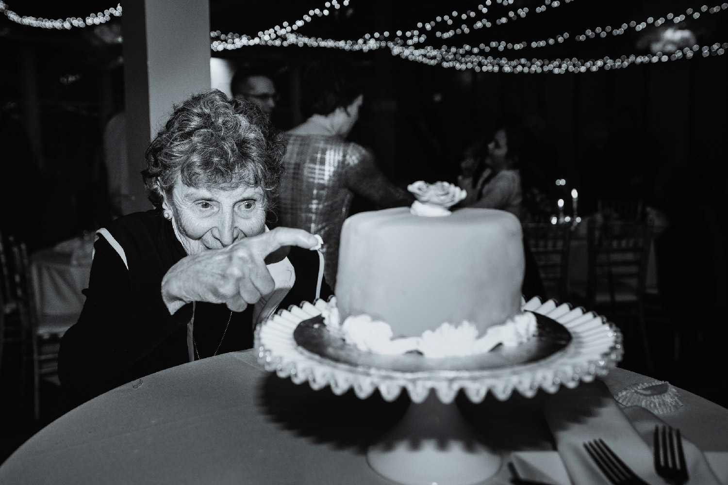 Older wedding guest sticking finger in cake to steal icing at reception Buffalo Wedding Photographer Jacqueline Connor Photography