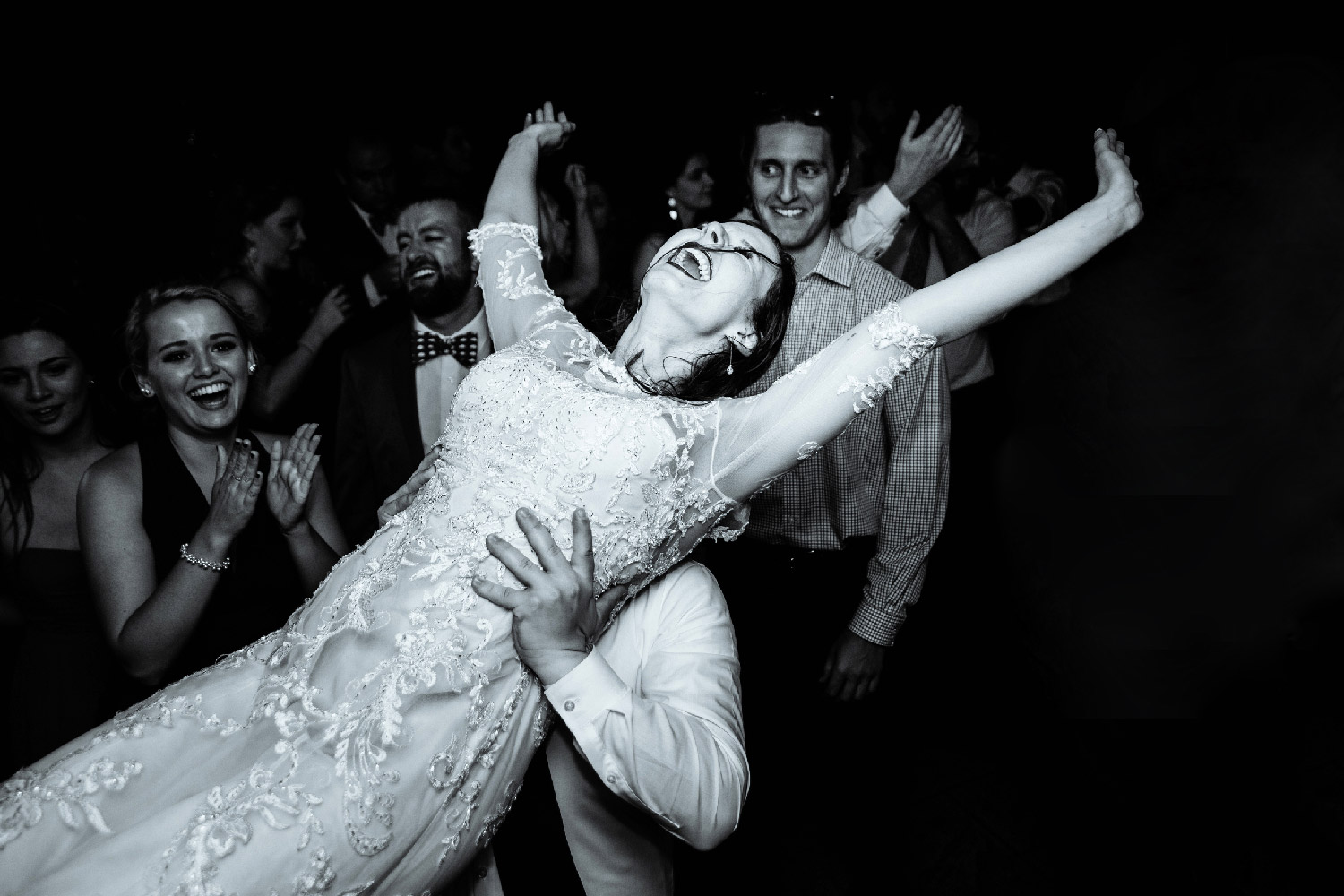 Wedding guests lift bride in long-sleeved lace wedding dress up in air on dance floor at reception Buffalo Upstate New York Wedding Photographer Jacqueline Connor Photography