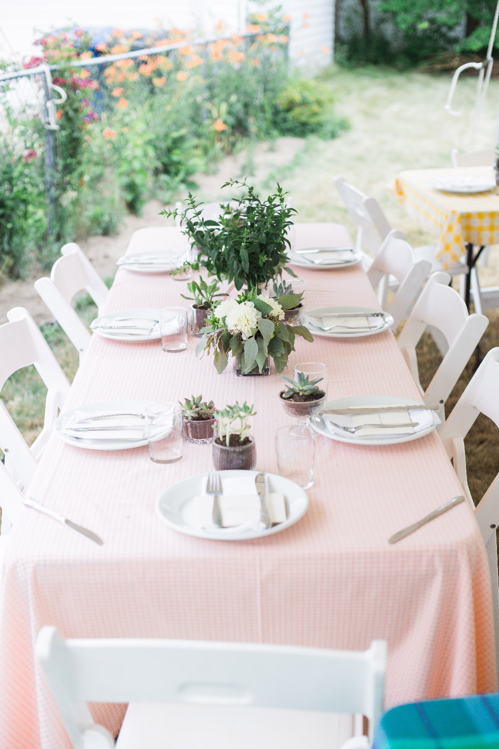 Wedding reception table with pink checked table cloth and simple modern florals and centerpieces in backyard of Cleveland Ohio home Lea Marie Photography