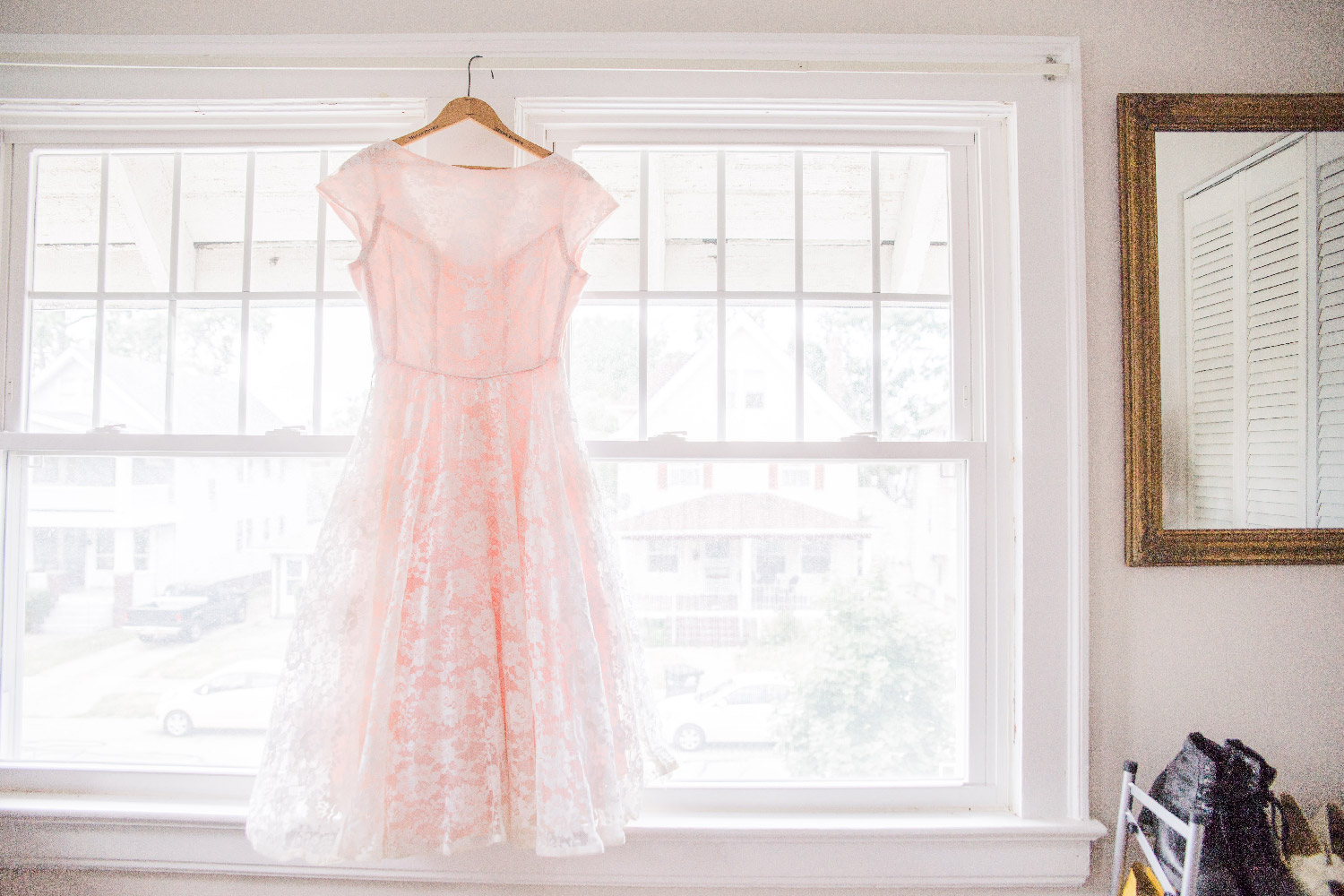 Bethany's pink lace wedding dress hanging in window of their Cleveland Ohio home Lea Marie Photography