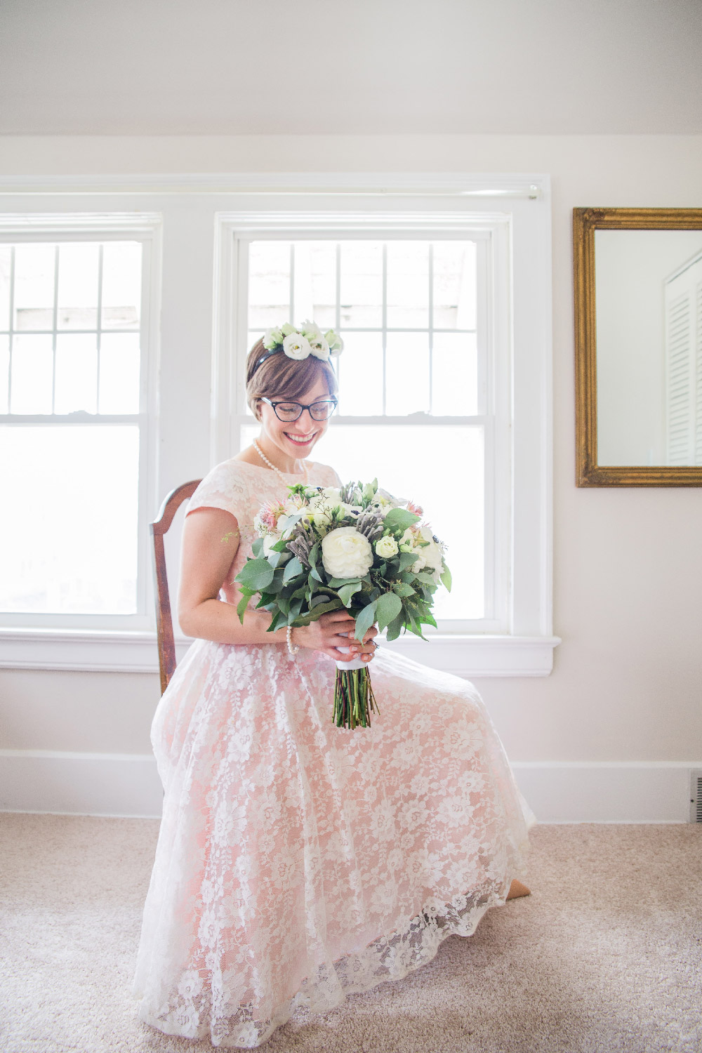Bethany sitting in chair wearing pink lace wedding dress holding bouquet and wearing flower crown Cleveland Ohio Lea Marie Photography
