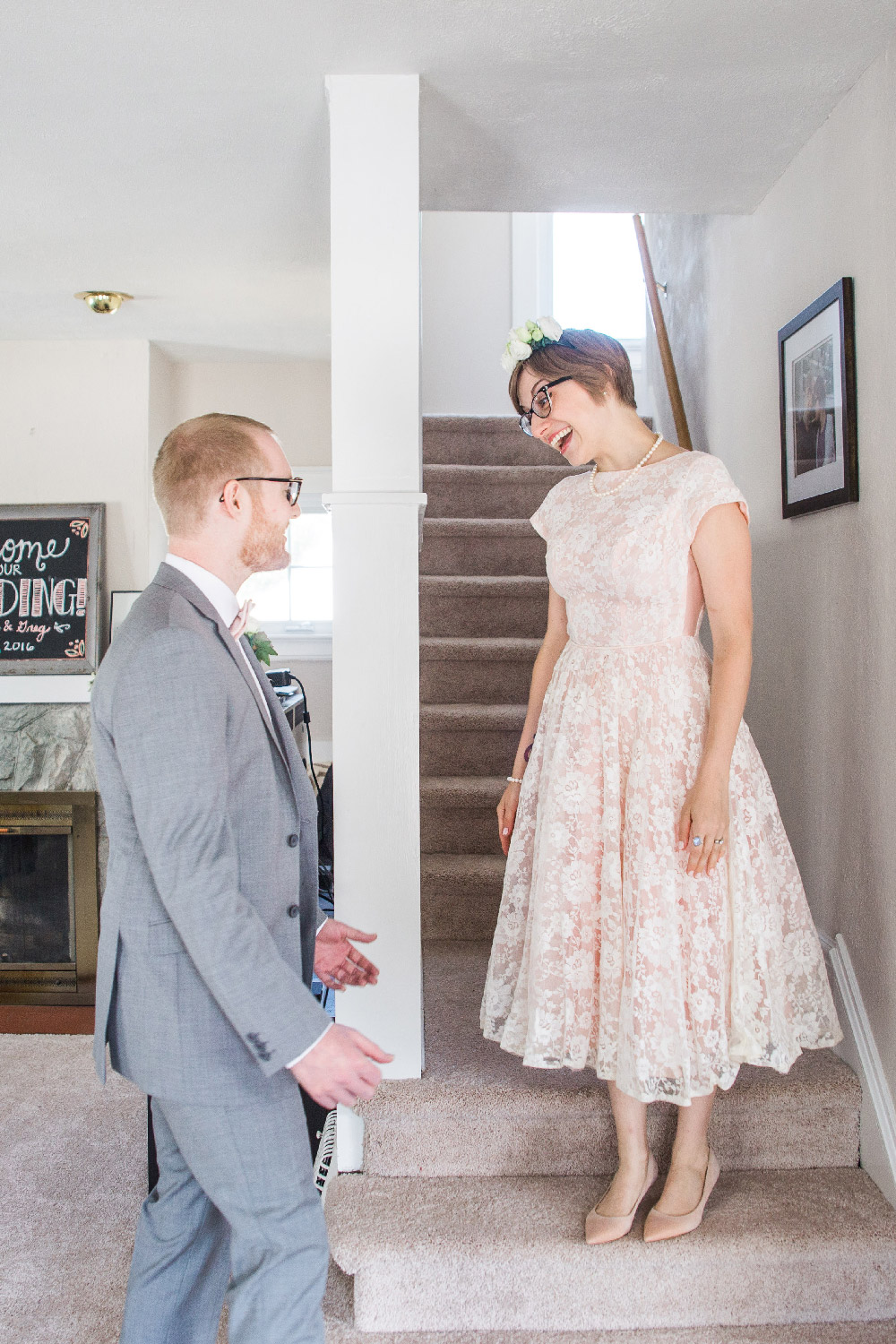 Bethany and Greg's wedding first look as bethany comes down the stairs in their Cleveland ohio home Lea Marie Photography