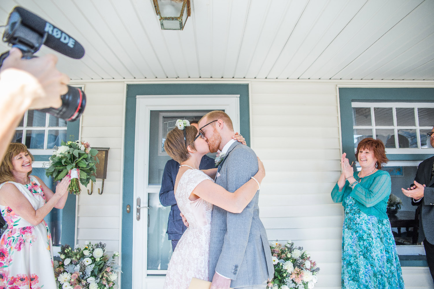 Newlywed couple Bethany and Greg kiss during their front porch ceremony of their Cleveland Ohio home Lea Marie Photography