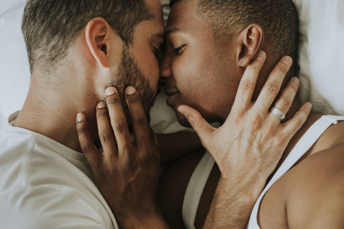 two married men embraced in bed