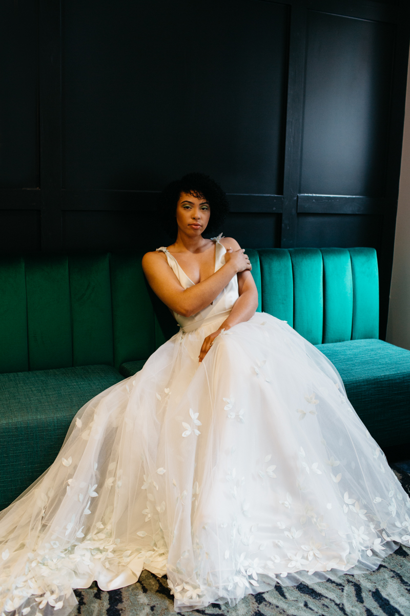 wes anderson inspired wedding styled shoot columbia south carolina bride lounging on bench seat, full shot of gown