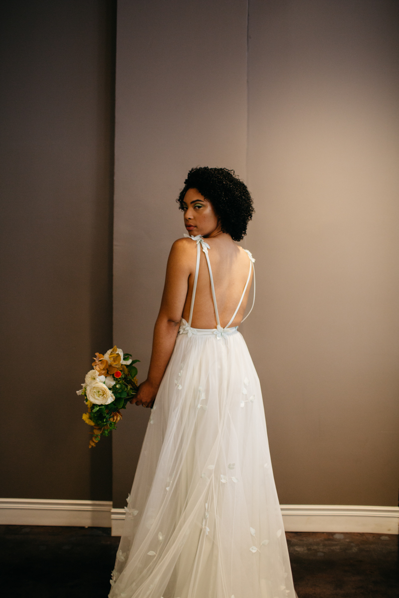 wes anderson inspired wedding styled shoot columbia south carolina bride looking over shoulder holding bouquet, back of gown featured