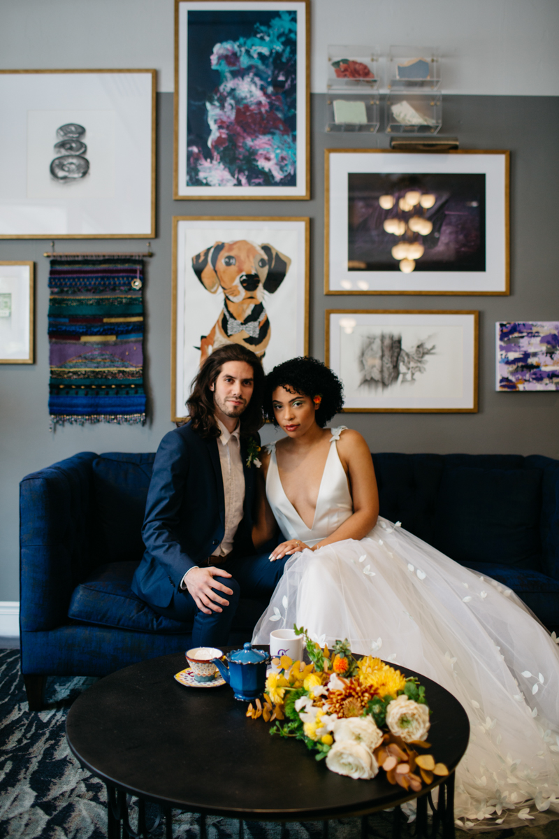 wes anderson inspired wedding styled shoot columbia south carolina bride and groom on sofa, bouquet and mismatched tea set on table, portraits on wall behind them