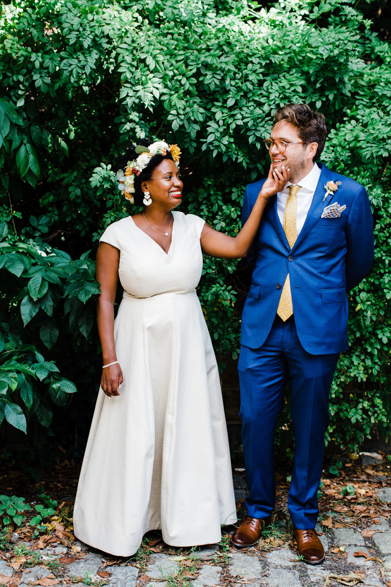 Starsha cupping Andrei's chin in front of greenery. Starsha is long white gown and DIY floral crown Andrei in blue suit