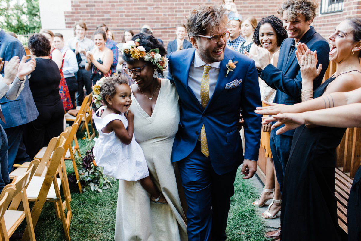 Starsha and Andrei walk up aisle with their daughter in their arms surrounded by cheering guests