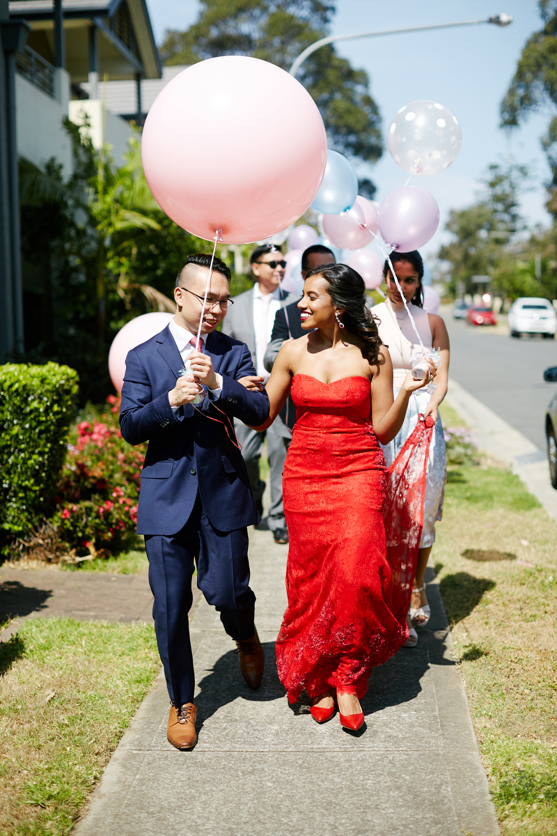 Hasara and Daniel walking down sidewalk with family and giant balloons to wedding tea ceremony in Sydney Australia