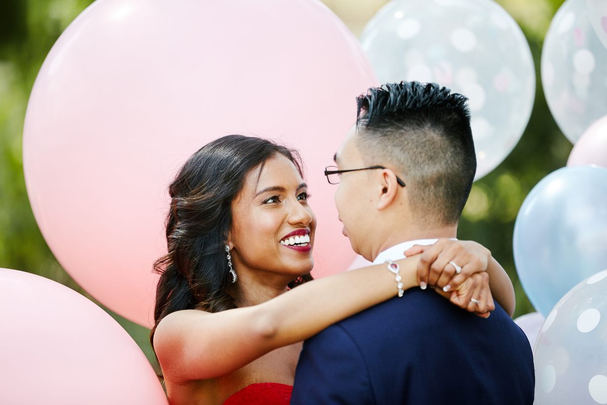 Hasara and Daniel hugging and smiling in front of large pink balloons before their wedding in Sydney Australia