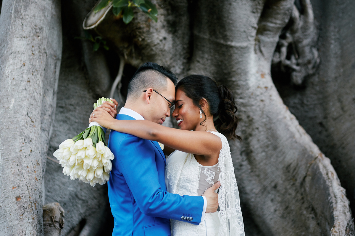 Hasara and Daniel hugging in front of tree before their Sri Lankan wedding ceremony in Sydney Australia