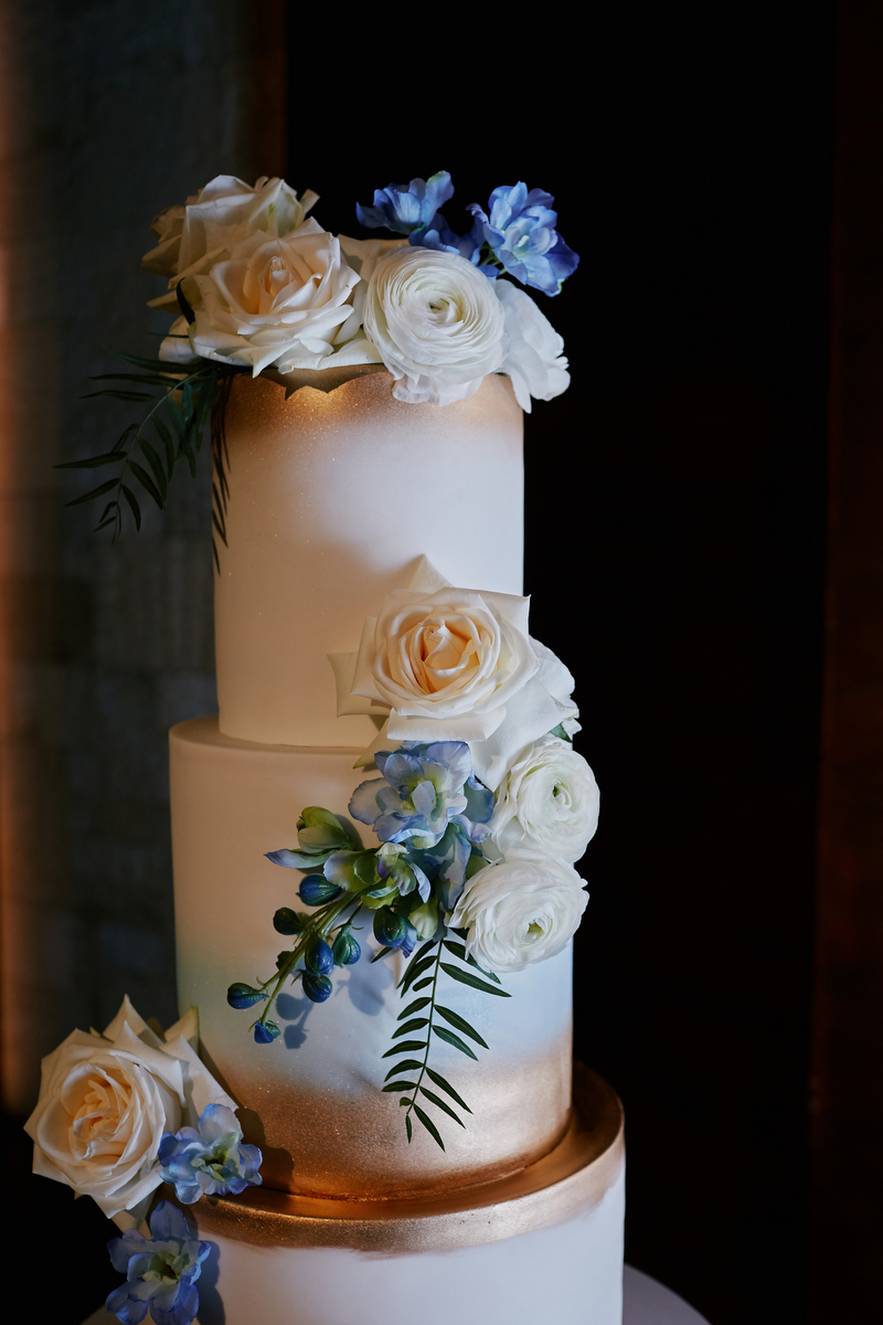 white wedding cake with gold accents roses and pops of blue flowers