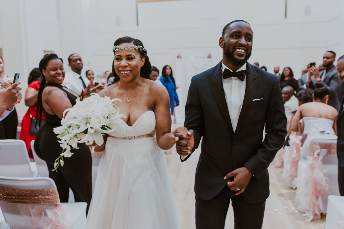 Shavonne and Travis walking up the aisle smiling and holding hands after getting married at The Levine Museum of the New South