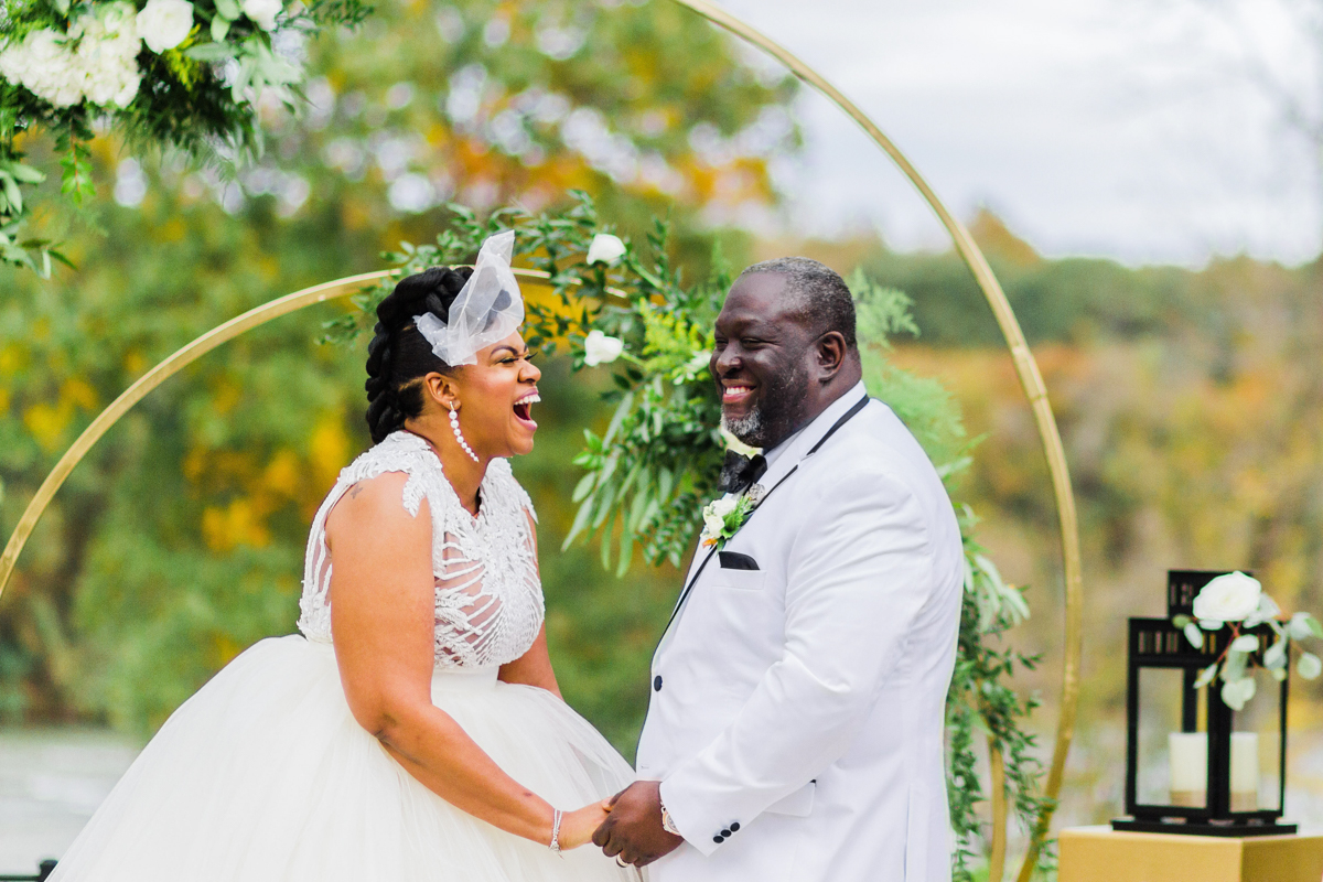 glam wedding river walk south carolina couple laughing at altar