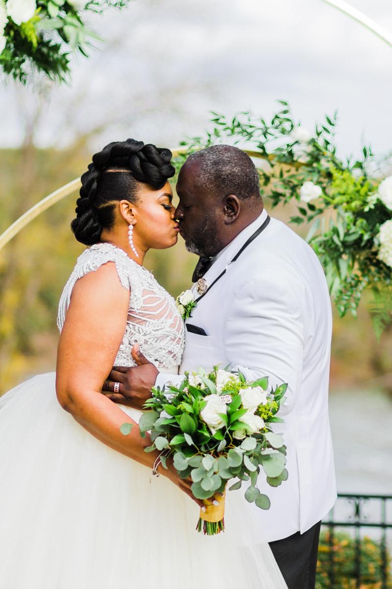 glam wedding river walk south carolina kiss at altar