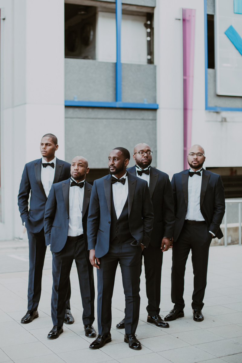 Travis and his groomsmen standing together in black suits with black bow ties in front of colorful building