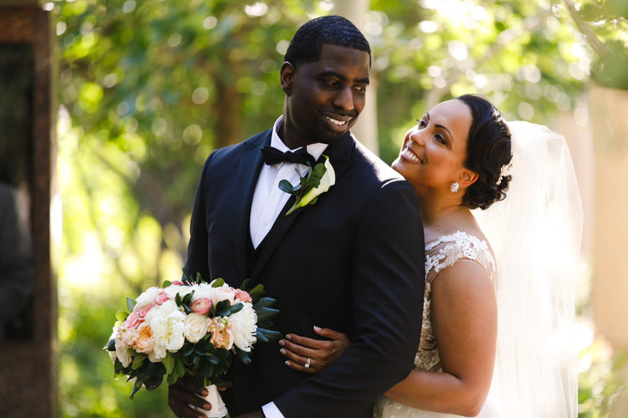 african american, christian, and muslim traditions minneapolis wedding taara standing behind glenn, smiling at one another