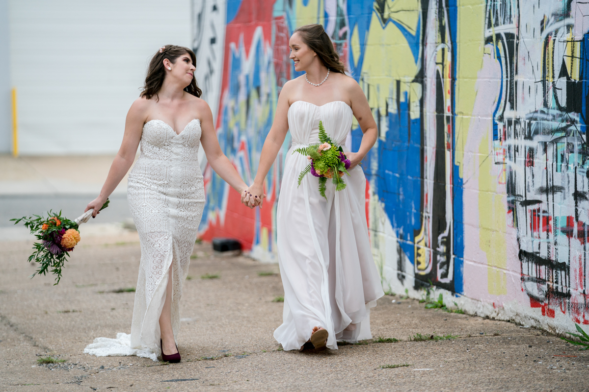 Brewery wedding washington D.C. brides walking hand in hand down street past mural