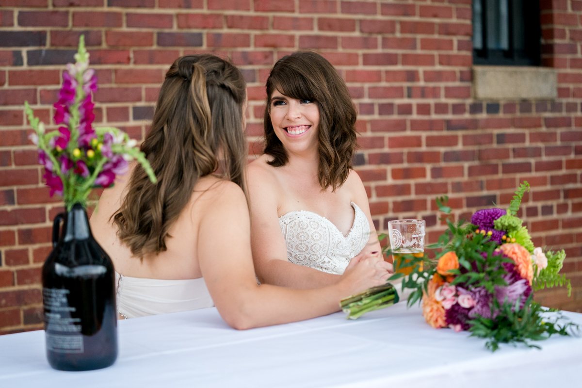Brewery wedding washington D.C. brides at main table with glass of beer
