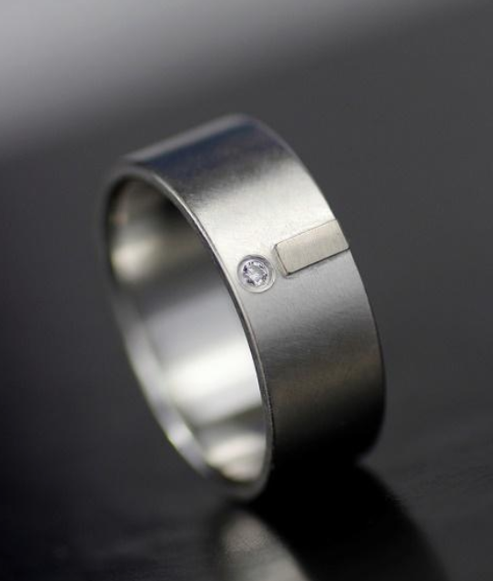 silver wedding band with silver tab and inset diamond