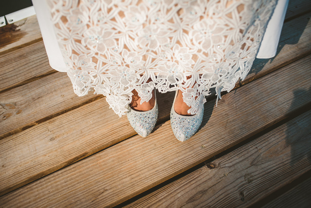 wedding inspiration the boathouse at sunday park midlothian virginia bride's shoes as she stands on dock