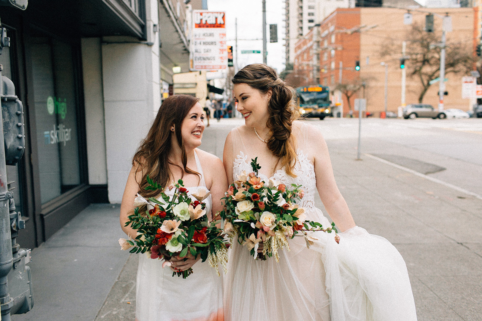 andrea and leigh walking down sidewalk smiling at each other in wedding dresses with floral bouquets after their wedding seattle washington fuck yeah weddings kendall shea