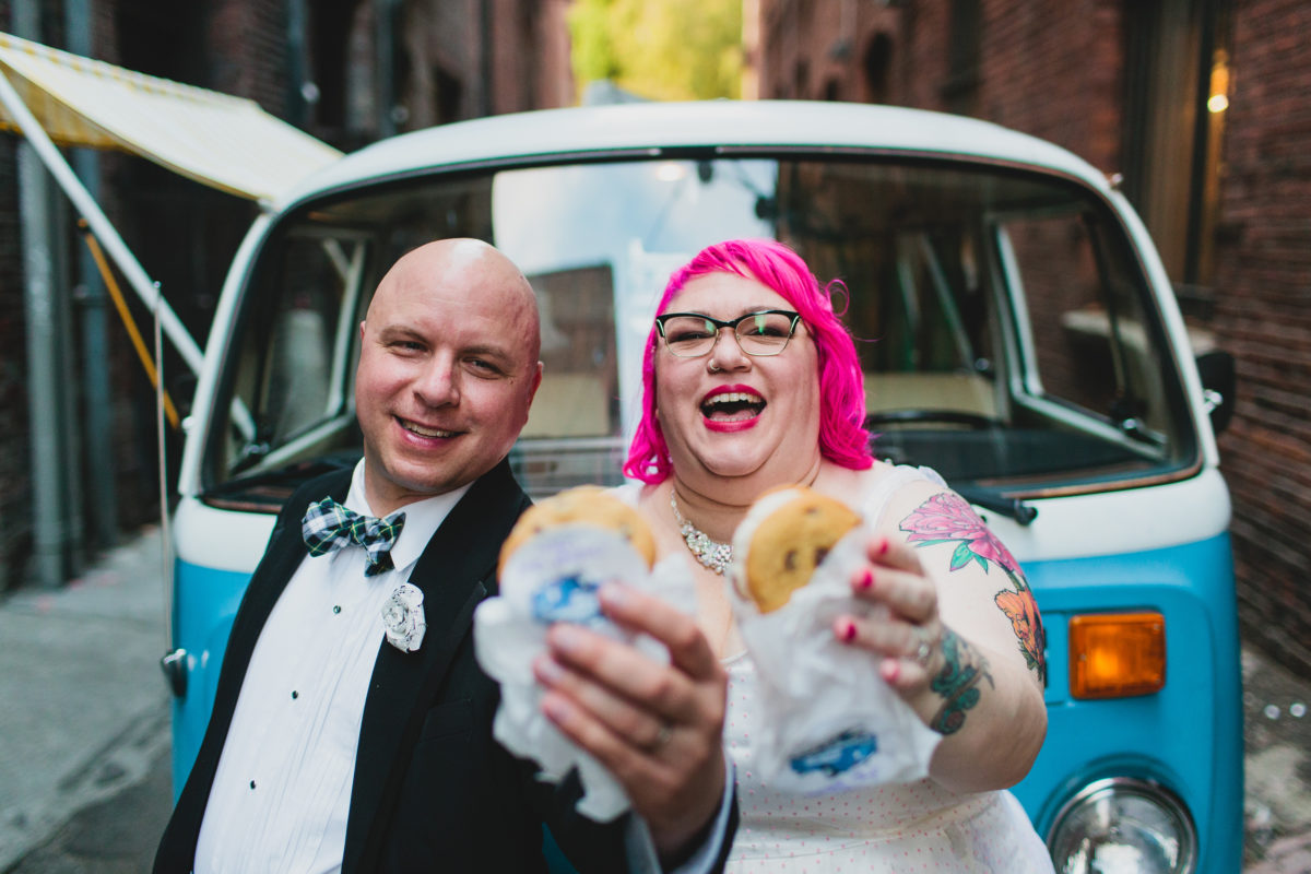 newlywed couple smiling and holding up ice cream cookie sandwiches after their wedding in front of a blue vw van fuck yeah weddings seattle washington