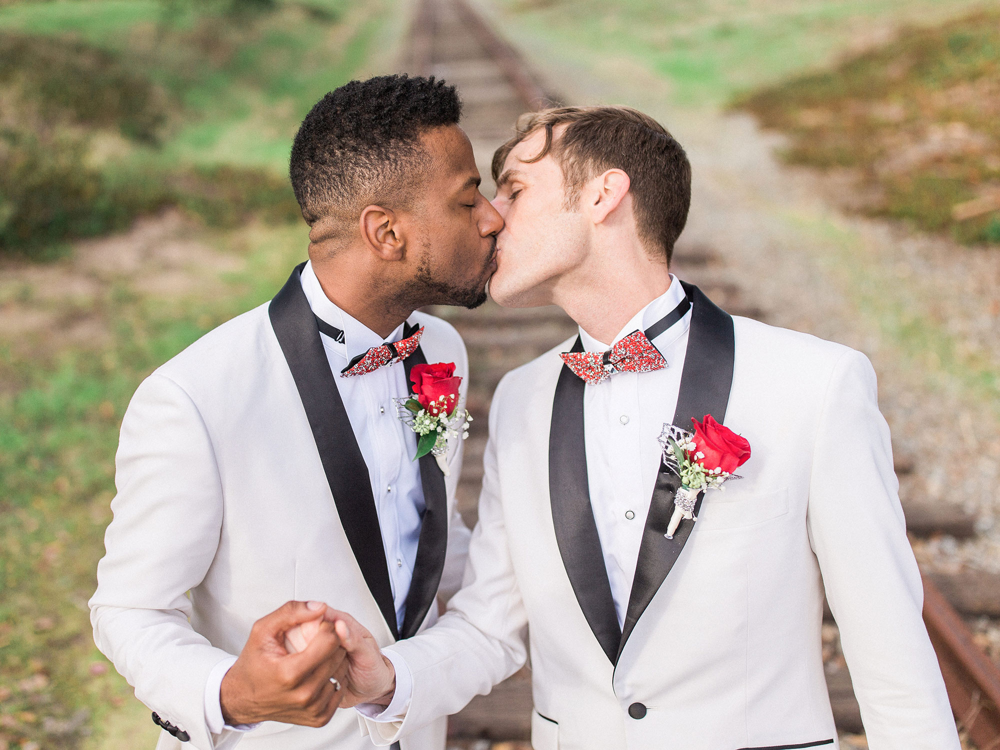 two grooms in matching suits kissing and holding hands in a field after their wedding Apollo Fotografie San Francisco