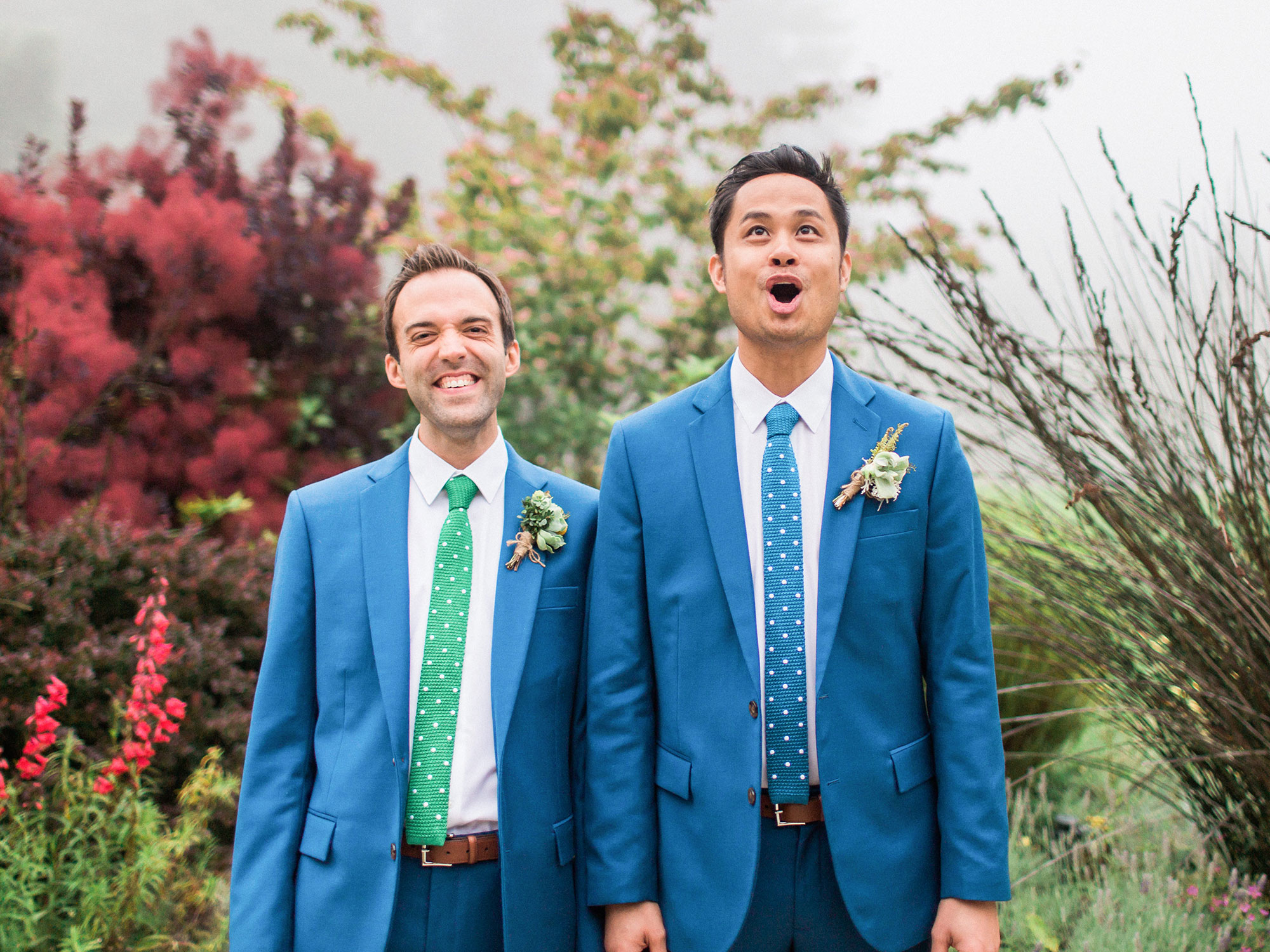 two grooms in matching suits holding hands and smiling at their wedding Apollo Fotografie San Francisco