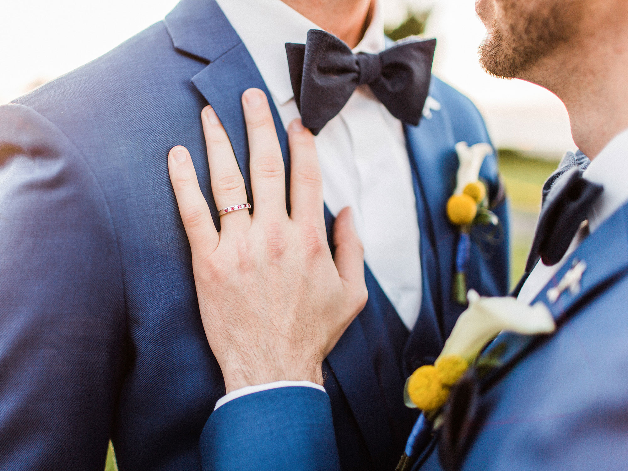two grooms in matching suits embracing at their wedding Apollo Fotografie San Francisco