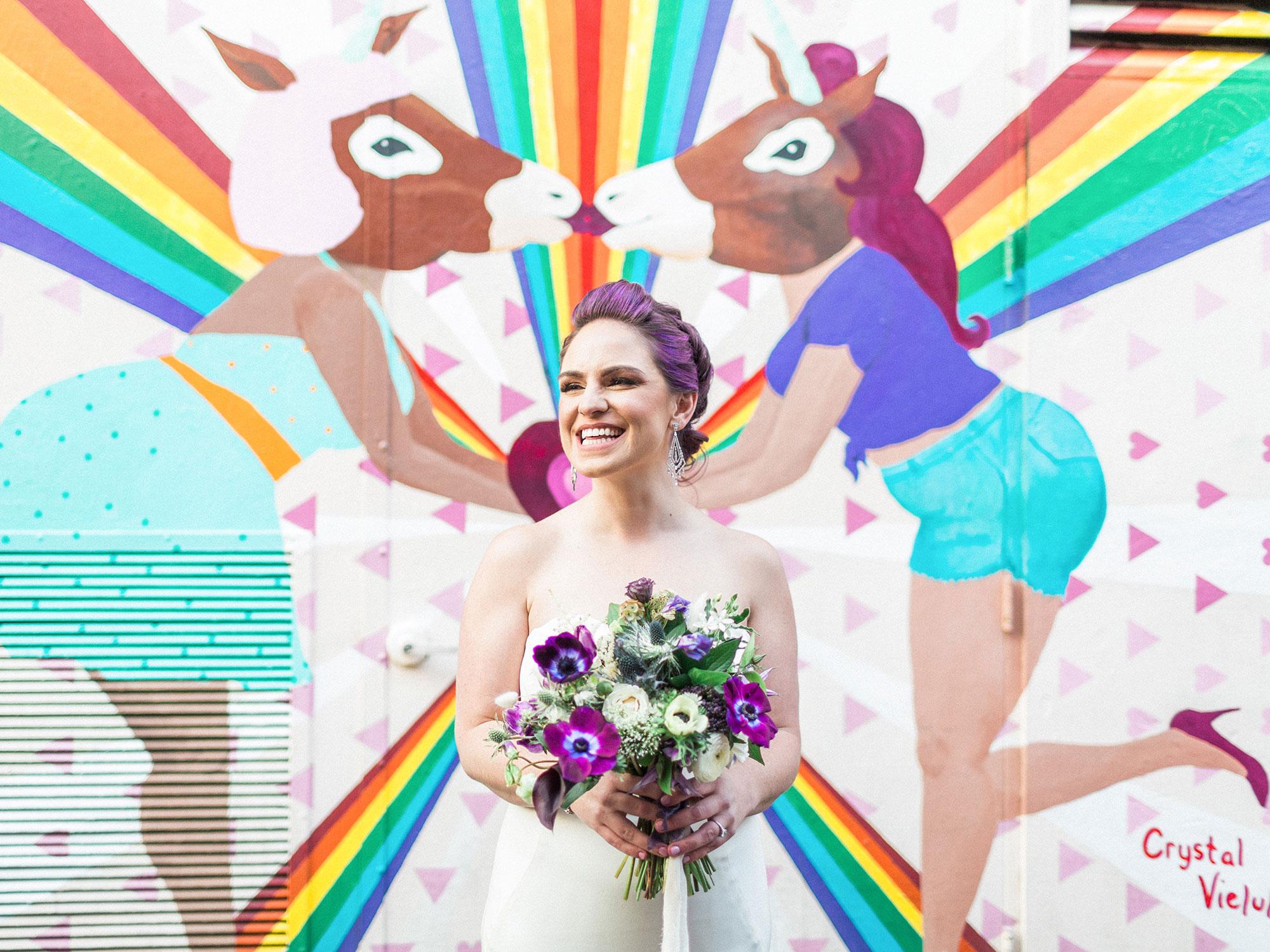bride holding bouquet in front of rainbow unicorn mural Apollo Fotografie San Francisco