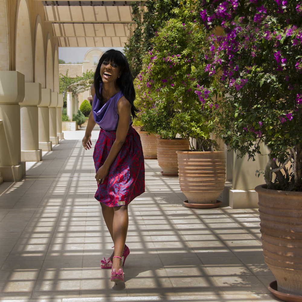 Nova reid of Nu Bride walking down covered path in a purple and pink dress