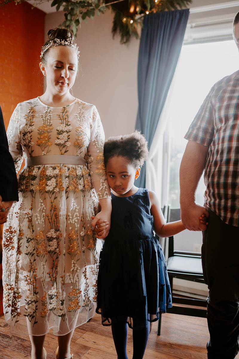 queer surprise home wedding little girl looking at camera during prayer circle, holding jess's hand