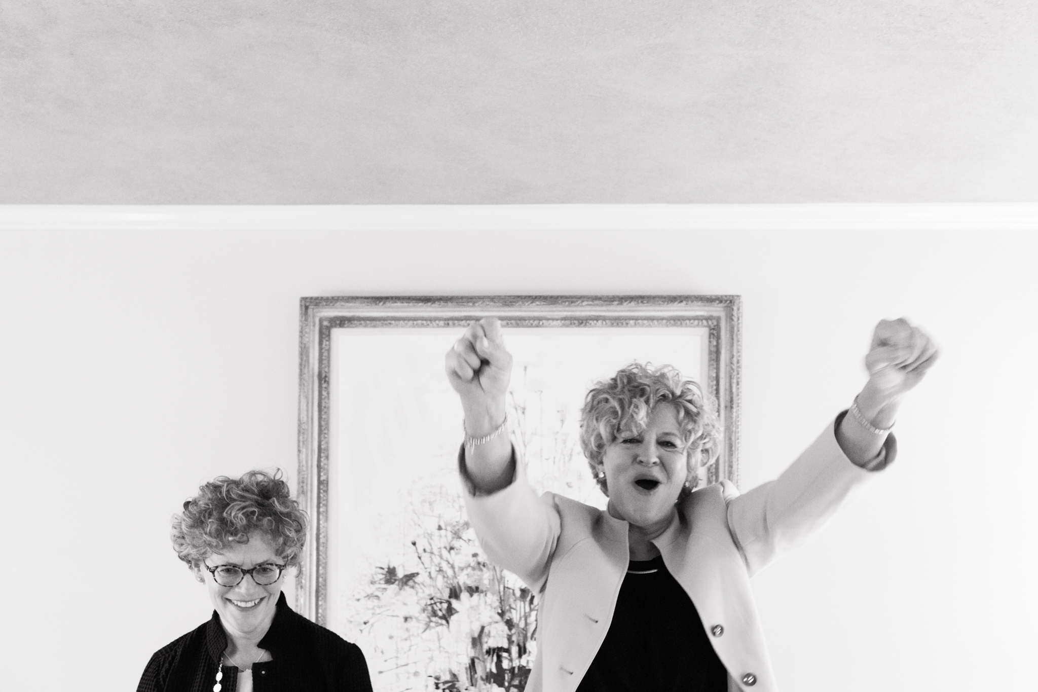 two brides excited and raising arms up in the air after exchanging their vows at their casual wedding Meera Graham Photography Missoula Montana