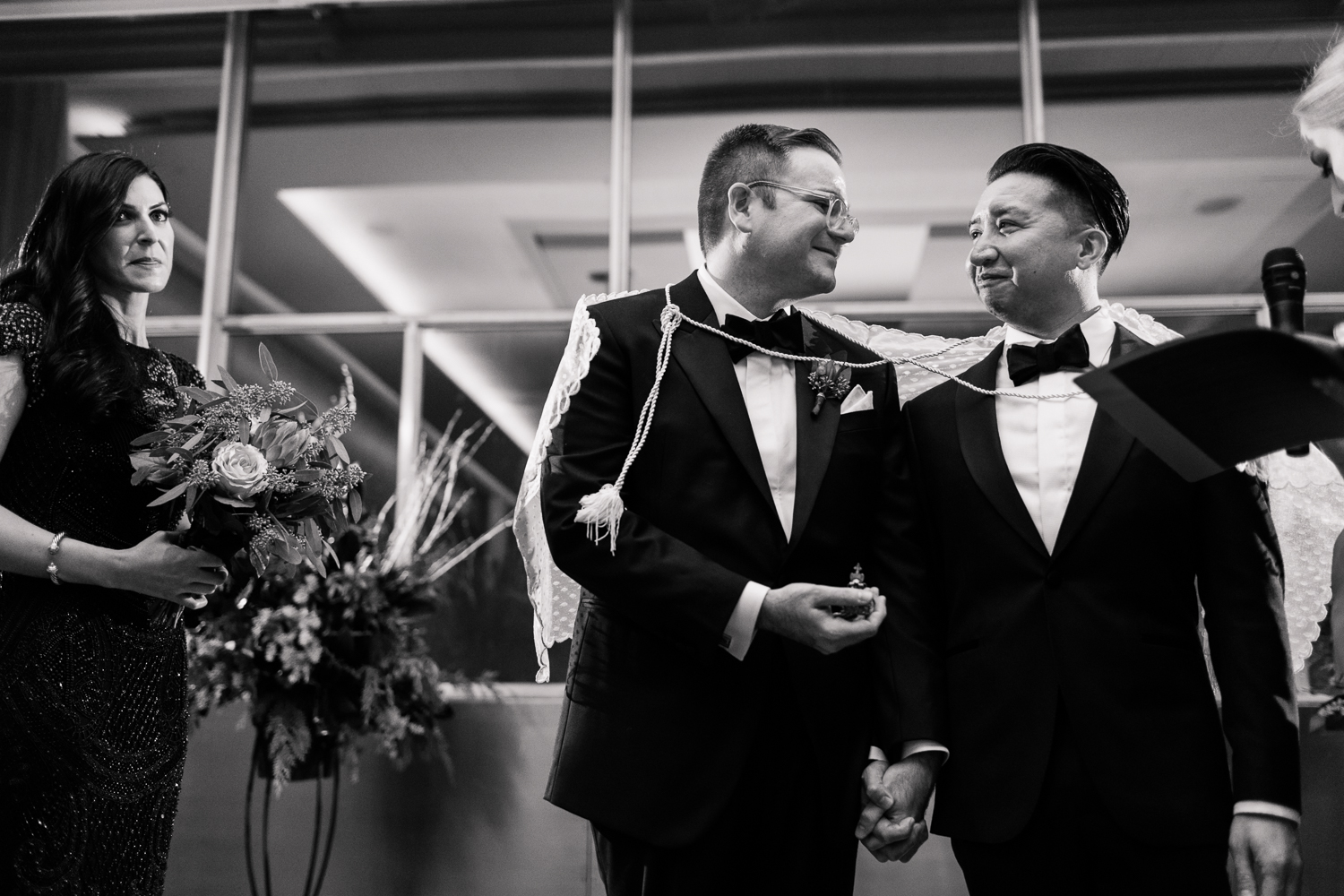 two grooms bound together and exchanging vows while holding hands during their wedding ceremony Meera Graham Photography Missoula Montana