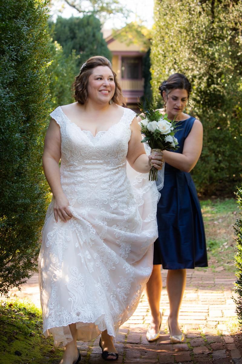 Romantic, Intimate-Feeling Wedding caroline walking down brick path with bridesmaid holding train