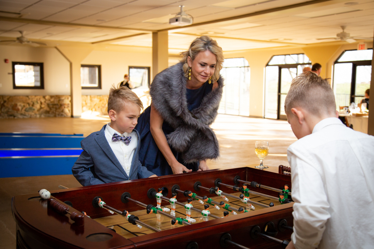 Romantic, Intimate-Feeling Wedding bridesmaid playing foosball with young guests