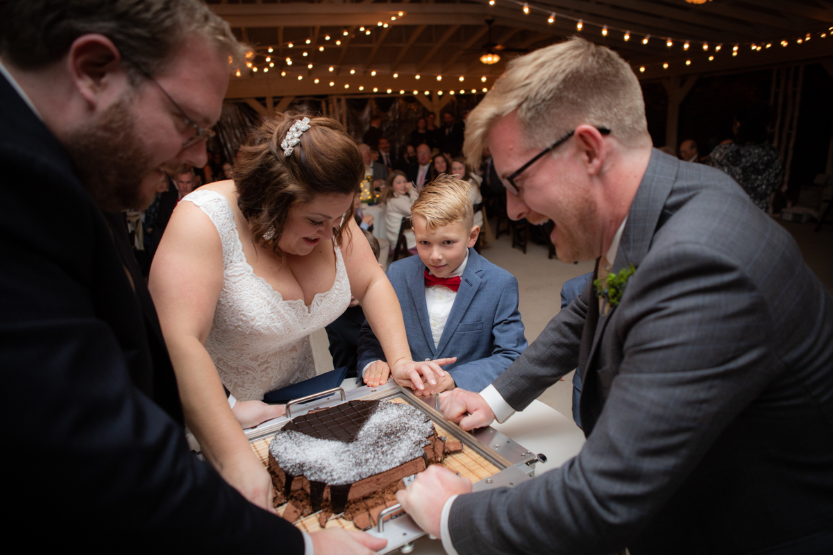 Romantic, Intimate-Feeling Wedding couple getting help with cake cutter from friend and young guest