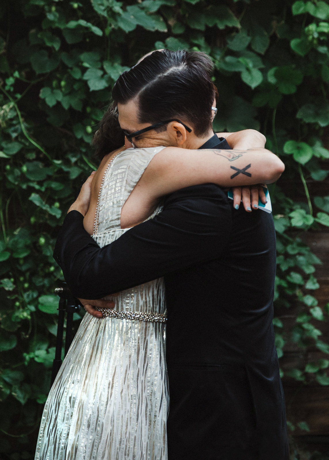 newlywed couple hugging and embracing after wedding ceremony by Austin Texas LGBTQ friendly photographer Ziggy Shoots