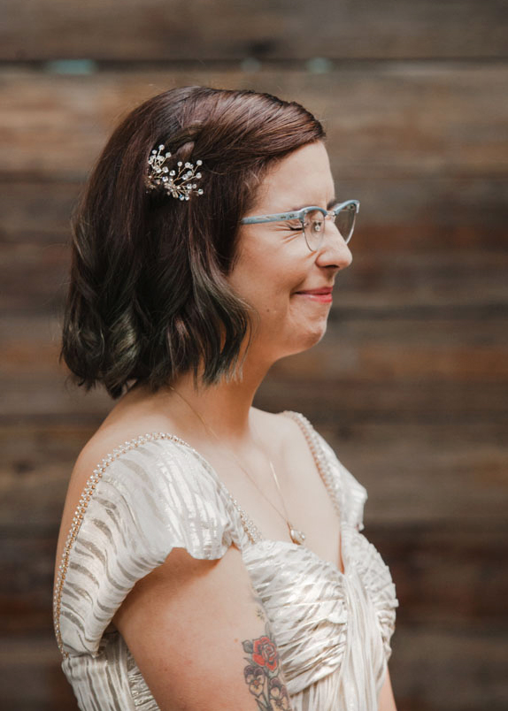 Bride with vintage style and tattoos smiling during wedding ceremony by Austin Texas LGBTQ friendly photographer Ziggy Shoots