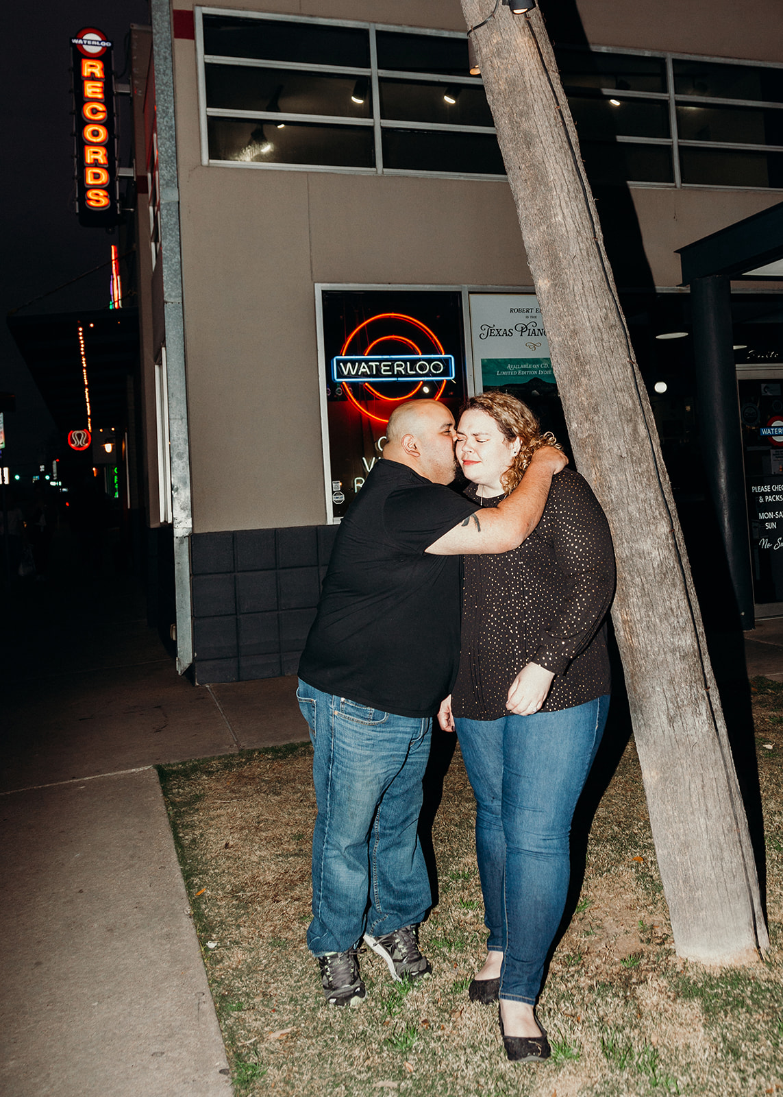 Sharing a kiss on the cheek at an intimate and laid back couples engagement shoot at Waterloo Records by Austin Texas LGBTQ friendly wedding photographer Ziggy Shoots