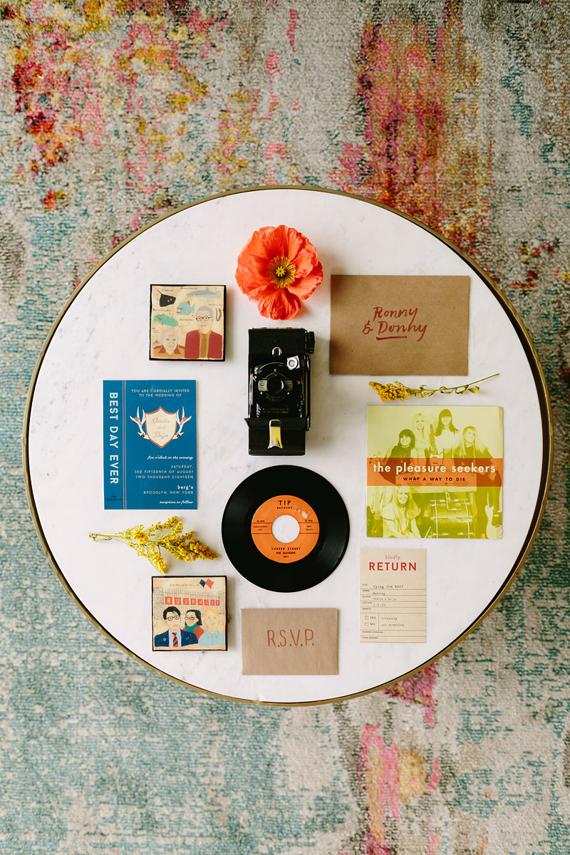 wes anderson inspired wedding brooklyn new york invitation and rsvp on table with flowers, old camera, and a vinyl record