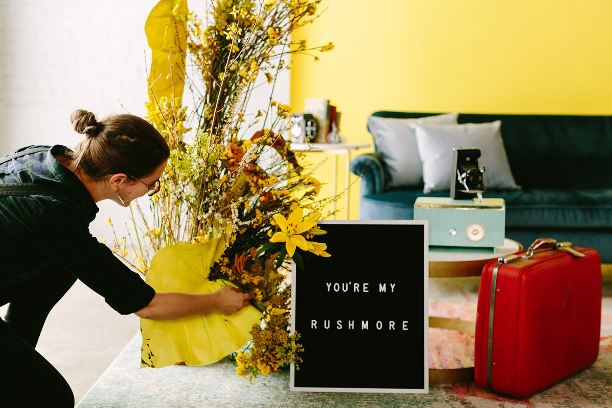 """wes anderson inspired wedding brooklyn new york arranging flowers near letterboard sign reading """"you're my rushmore"""""""