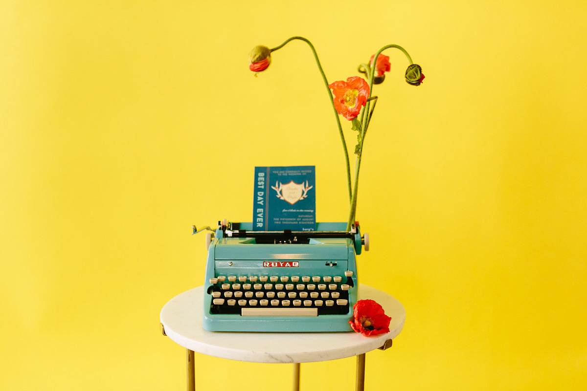 wes anderson inspired wedding brooklyn new york typewriter with invitation against bright yellow background