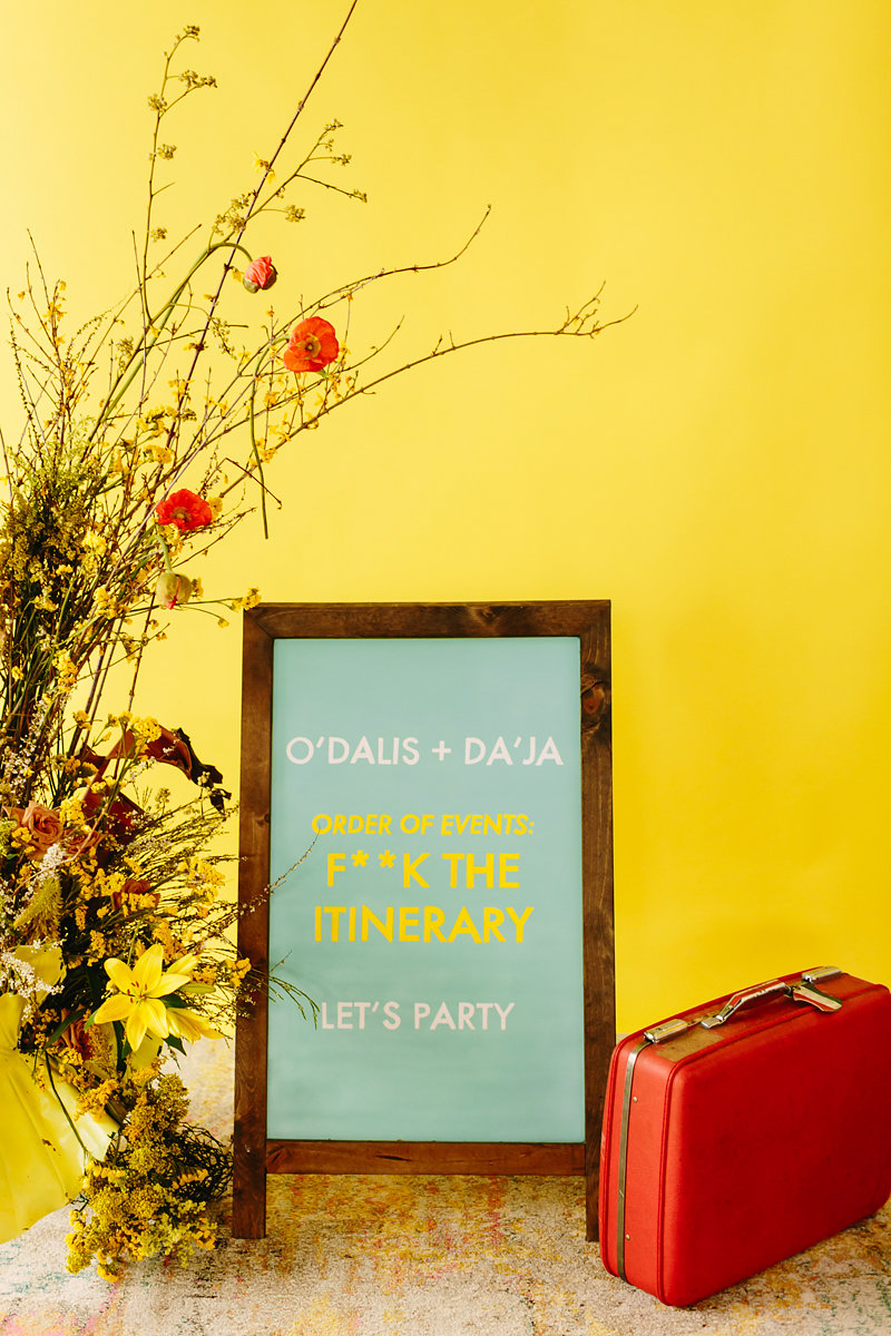 """wes anderson inspired wedding brooklyn new york sign reading """"""""o'dalis + da'ja order of events: f**k the itinerary, let's party"""""""