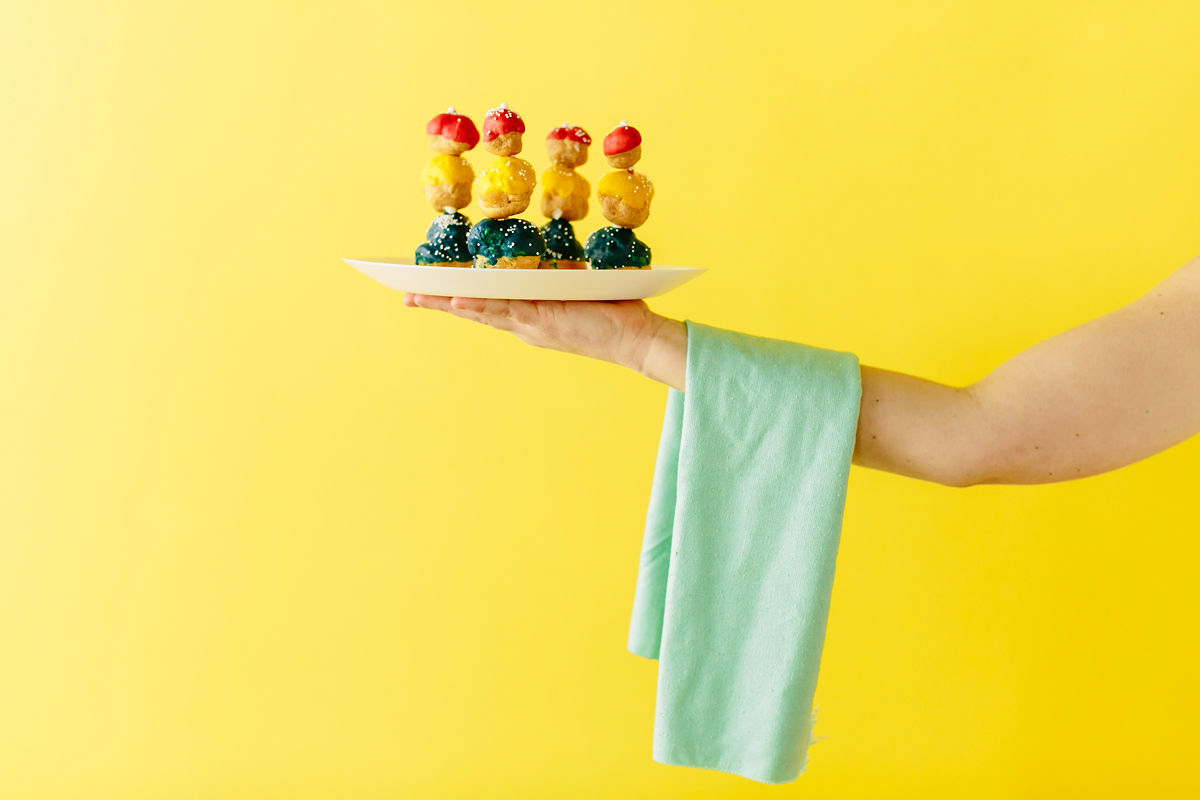 wes anderson inspired wedding brooklyn new york arm with towel draped over it holding desserts against bright yellow background