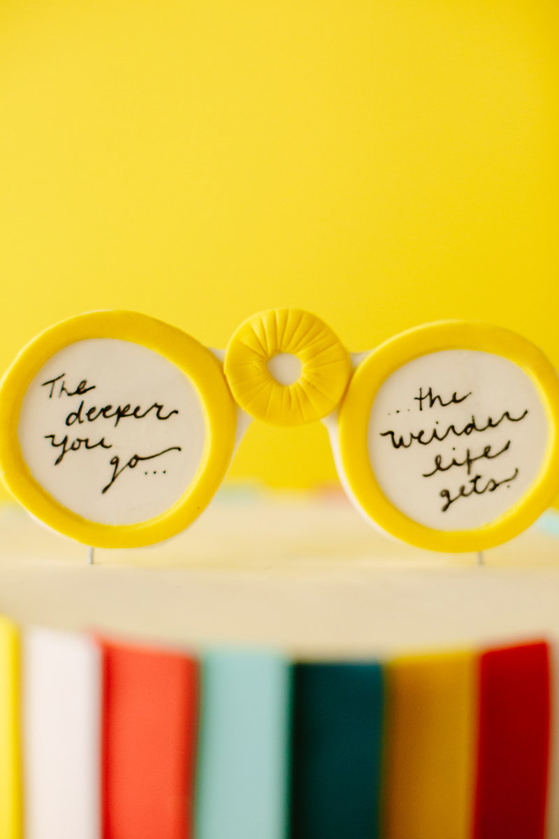 """wes anderson inspired wedding brooklyn new york cake topper shaped like glasses reading """"the deeper you go… the weirder life gets"""""""