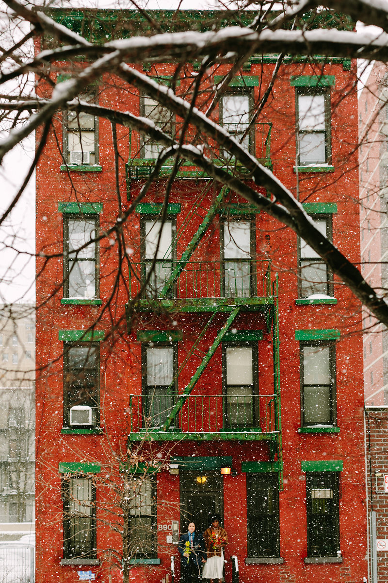 wes anderson inspired wedding brooklyn new york couple standing in doorway of venue while snow falls