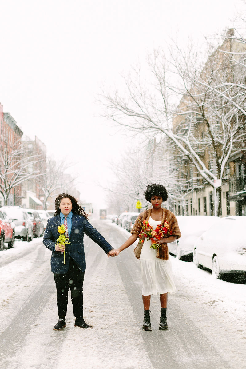 wes anderson inspired wedding brooklyn new york couple holding hands in snowy street, both holding flowers